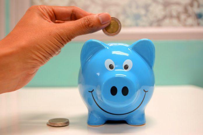 pessoa-guardando-moedas-no-cofre-de-porco-azul-dicas-para-juntar-dinheiro