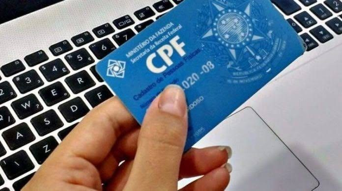 teclado-computador-mao-segurando-cartao-cpf-cadastro-positivo