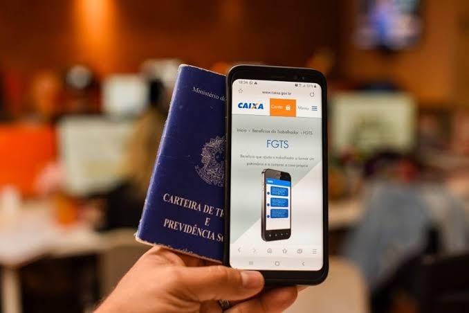 mao-segurando-celular-e-carteira-de-trabalho-fgts-saque-aniversario-do-fgts
